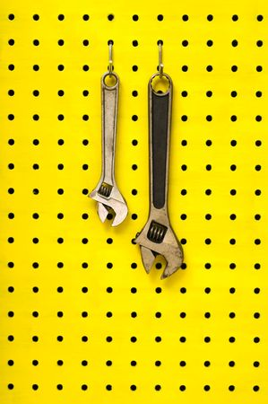 pegs: Pair of metal wrenches (spanners) hang together off of hooks on yellow pegboard. Stock Photo