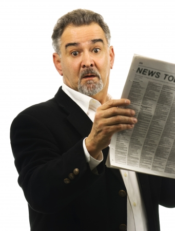 well read: A mature man looks surprised; shocked; awestruck while reading a newspaper. Stock Photo
