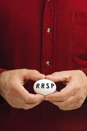 A man holds an egg with RRSP written on it. photo
