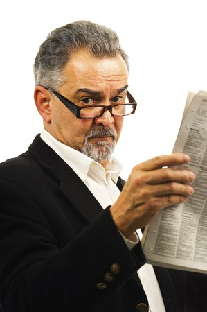 An older businessman with glasses holds up a newspaper. photo
