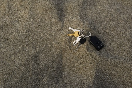 House and car keys on a ring with a remote left in the sand. Stock Photo