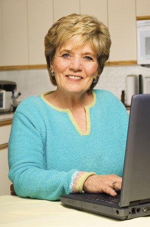 typing on computer: A senior woman smiles while working on her laptop in her kitchen Stock Photo