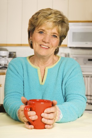 A happy, senior woman sits in her kitchen holding a red coffee mug.