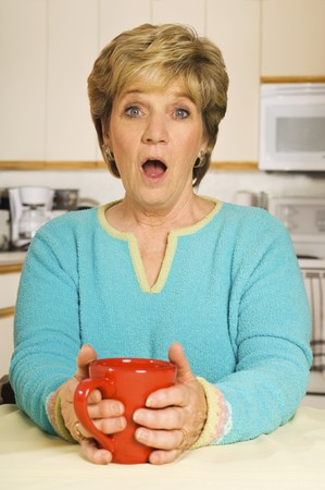 Senior woman, holding a coffee mug in her kitchen, with a look of shock on her face. Standard-Bild