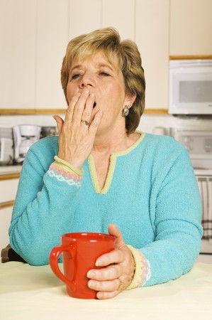 Senior woman yawns while sitting at her kitchen table with a coffee mug Standard-Bild