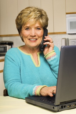 Working from home, a senior woman multitasks: takes a phone call while working on laptop, all at her kitchen table.