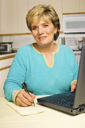 Senior woman sits in her kitchen with a laptop on the table, writing down some notes.