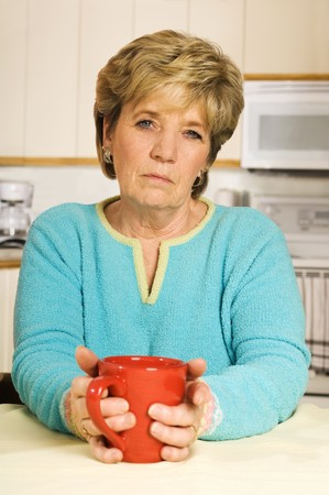 worry: Senior woman holds a coffee mug, looking unhappy.