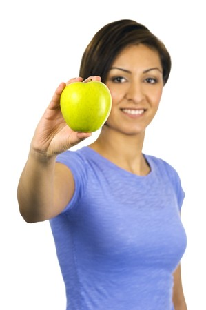 A young ethnic woman holds out a green apple. photo