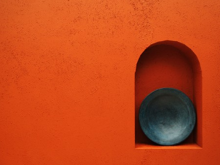 A blue plate sits in an alcove of a red-orange terra cotta wall.