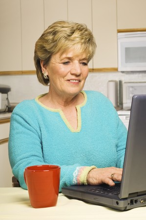 Senior woman works on her laptop in her kitchen, coffee mug at the ready. Stock Photo