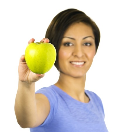 A young ethnic woman holds out a green apple.
