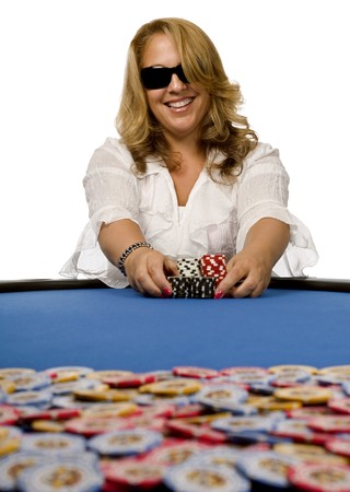 Attractive blonde woman pushes poker chips towards pot on blue felt table.