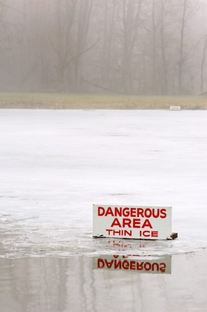 A pond covered in a thin layer of ice with some open water, and a sign signifying the danger during a foggy day. Standard-Bild