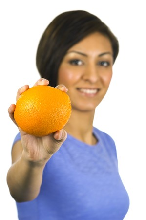 Pretty, young ethnic woman holds an orange.