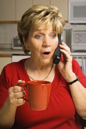 cordless phone: Senior woman, holding a red coffee mug, talks on the phone with a look of shock and surprise on her face.