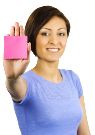 A pretty, young ethnic woman has a sticky note stuck on the palm of her hand. Photographed with a white background of +2 EV. Stock Photo