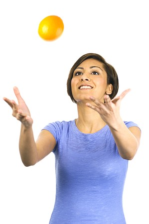 A young, ethnic woman plays catch with a ripe orange. Stock Photo