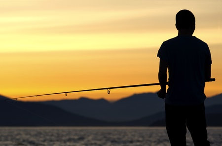 Vancouver, British Columbia, Canada - July 11, 2009 - A young man fishes in English Bay, overlooking the coastal mountains of B.C. at dusk. Editorial