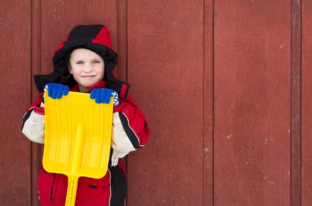 A young child, dressed in winter clothes, holds his plastic toy shovel while leaning against a red barn wall. Stock Photo