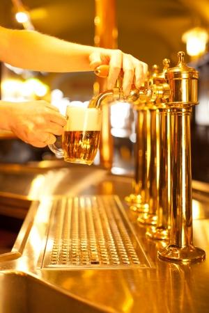 웨이터는 황금 마개에서 맥주 초안을 작성한다 스톡 콘텐츠
