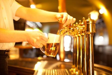 웨이터는 황금 수도꼭지에서 맥주 초안을 작성한다 스톡 콘텐츠