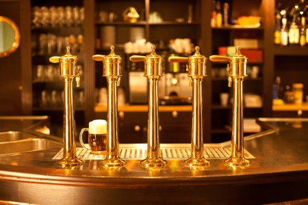 Luxury gold beer spigot at the brewery with a glass of beer photo