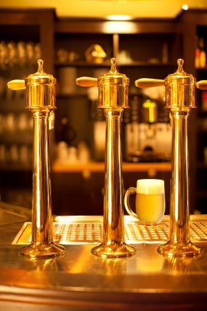 Luxury gold beer spigot at the brewery with a glass of beer Stock Photo - 23301744