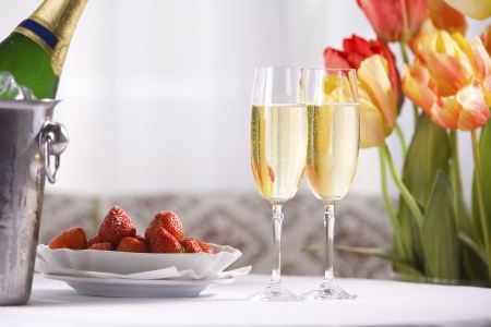 Spring still life with champagne  wine , strawberries and tulips photo
