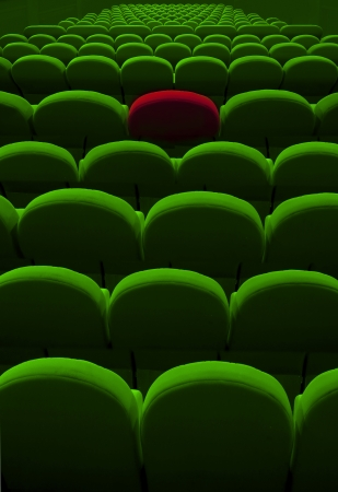 green cinema or theater empty seats with red one photo