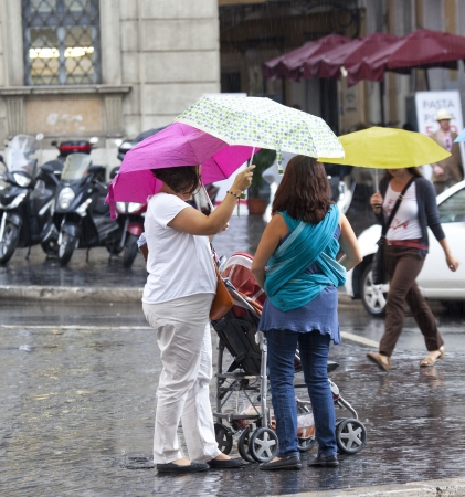 mothers with umbrellas are talking on the street Stock Photo - 23370513