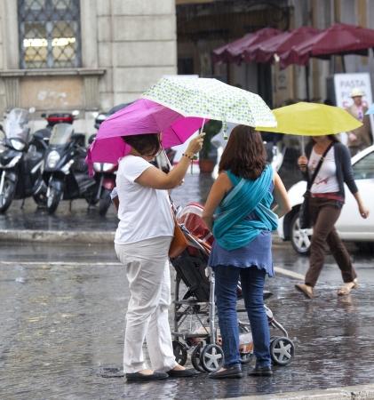 sidewalk talk: mothers with umbrellas are talking on the street