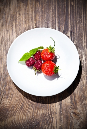 rapsberry and strawberry on whitte plate and wood table photo