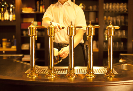 draught: gold beer in the hand and beer taps