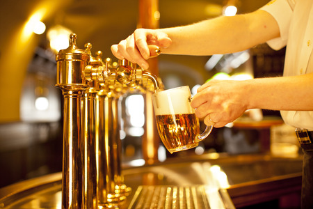 goud bier in de hand en biertaps Stockfoto