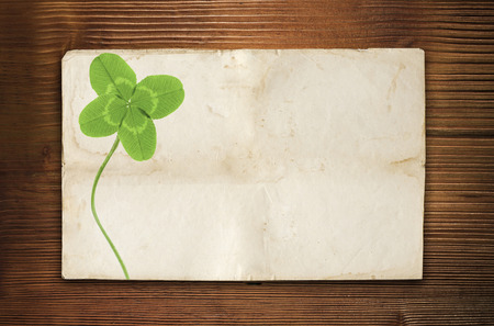 clover symbol on old wood background with empty paper photo