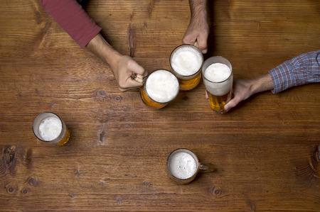 술집에서 나무 테이블에 맥주를 마시는 삼명