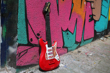 riff: guitar leaning against a colored wall Stock Photo