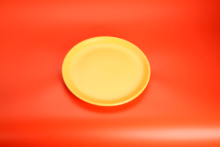 yeallow empty  plate on red table