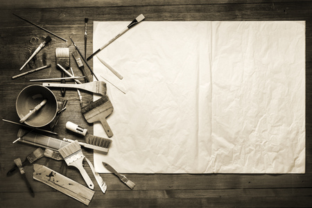 painting still life with paper, brushes and other tools on a wooden background