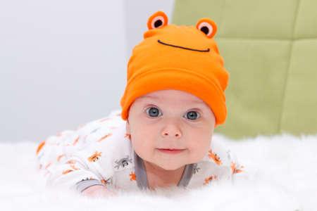 white fur: Baby lying on a white fur with orange cap