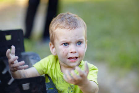 Little boy smeared his hands in the ashes and was surprised