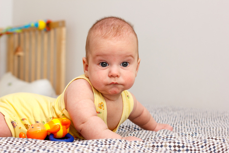 Happy three months old baby lying on a blanket on his stomach. Leans on his hands. Looking at the camera. Yellow.