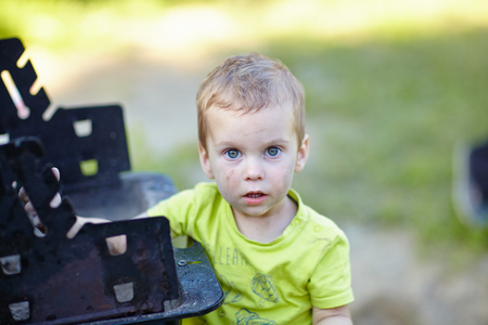 The little boy in green t-shirt soiled in ashes near campfire in the forest Stock Photo