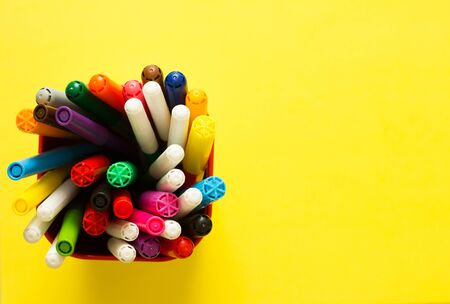 Collection of colored felt pen in cup on yellow background top view and copy space. Education, Back to school