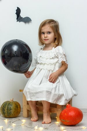 Helloween decoration. Cute little girl holding black ball, sitting on a bench on white background Stock Photo