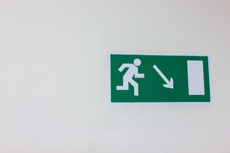 emergency green exit plate on the white wall