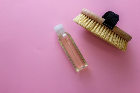 Spa organic brush for dry massage and a bottle of body oil on pink background. Cactus brush and Jar Of Vacuum Cellulite Massage. Anti-cellulite massage. Spa beauty concept.