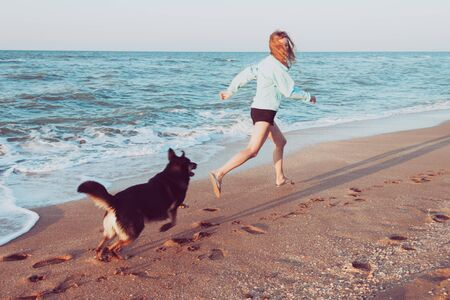Teenage girl running along a beach shore with black dog during the early morning.