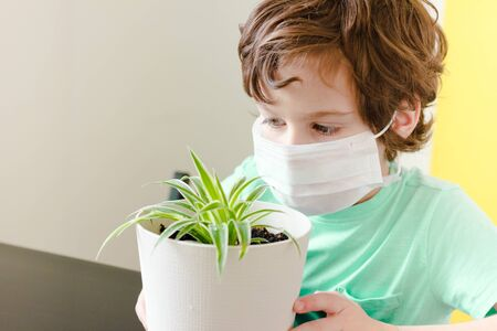 Curly boy in a medical mask holds a potted flower and looks out the window.